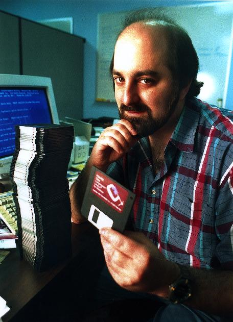 Phil Katz at his desk with a stack of floppy disks.